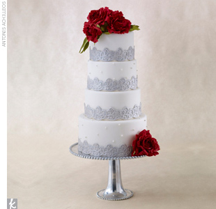 Four-tiered round wedding cake accented with silver fondant embellishment and sugar-made red roses.