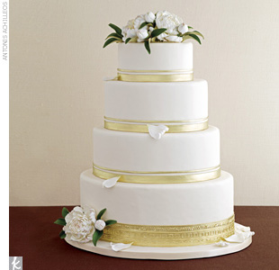 Four-tiered oval wedding cake banded in gold and accented with sugar-made peonies.