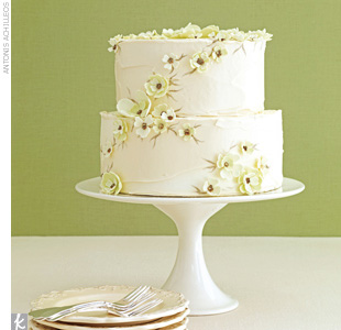 Two-tiered ivory buttercream wedding cake with soft green sugar flowers accented in gold.