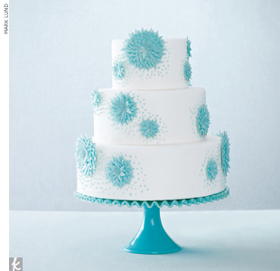 Three-tiered white wedding cake accented with light blue starburst sugar accents.
