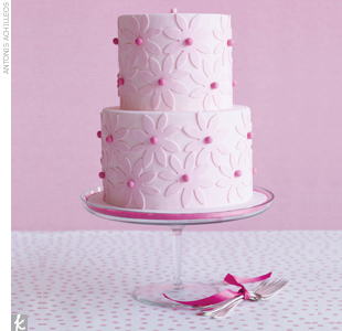 Two-tiered pink fondant wedding cake with fondant flower appliques.