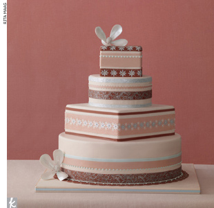 Four-tiered wedding cake stacked with a mix of round and square and accented with dots, starbursts, and other decorative patterns.