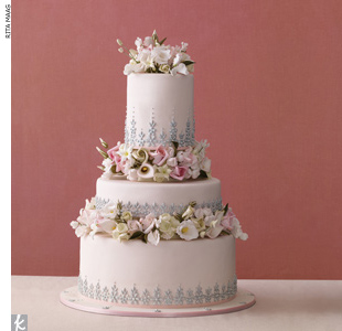 Three-tiered dusty pink fondant wedding cake accented with silver dragees and sugar flowers.