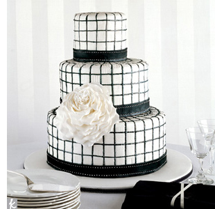 Black-and-white graphic tile cake accented with an oversized white sugar rose.