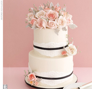 Two-tiered ivory fondant wedding cake accented with lace-inspired fondant accents and sugar flowers.