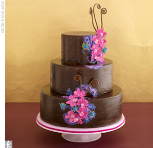 Three-tiered chocolate wedding cake accented with fuchsia and purple paper flowers and sugar-made fiddlehead fern.