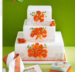 Three-tiered white fondant wedding cake accented with graphic paper patterned trim and orange orchid sugar flowers.