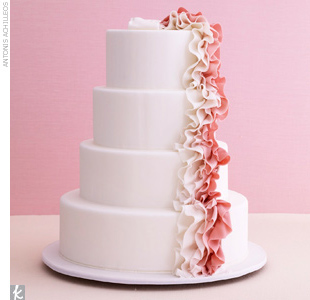 Four-tiered white fondant wedding cake accented with pink, blush, and white ruffled fondant ribbon.
