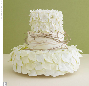 Three-tiered white and green wedding cake accented with sugar flowers, soft sugar-made branches, and leaves.