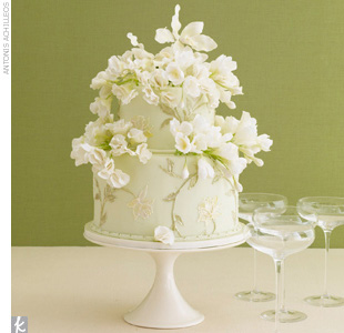 Two-tiered, soft green fondant wedding cake accented with gold painted flowers and white sugar flowers.