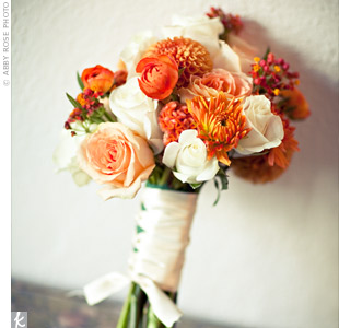 Adrienne carried a white, cream, and orange bouquet of dahlias (theyre in-season during the fall) and roses packed tightly and wrapped with brown ribbon.