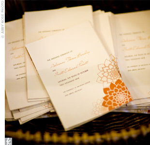 An orange dahlia inspired Adrienne and Scotts invitations and programs. The couple kept their design simple by using dahlias as the only visual element of the design.