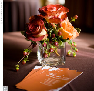 For the cocktail tables, Adrienne and Scott chose tiny centerpieces of red and orange roses, dahlias, and lilies in glass cubes for a simple but sweet, romantic look.