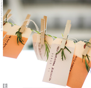 Elizabeth dipped plain manila tags in paint, wrote guests names, and table numbers on them and hung them with clothespins. To the tags, she tied rosemary she had spent all summer growing on her roof at work.