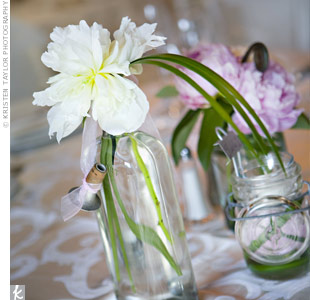 The barn was a historic venue, so Kelly and Dave couldn't hang anything on the walls. Instead they relied on table décor to convey the vintage-chic style. For the centerpieces, they gathered old bottles and jars from antique stores to hold one or two pink or white peonies each.