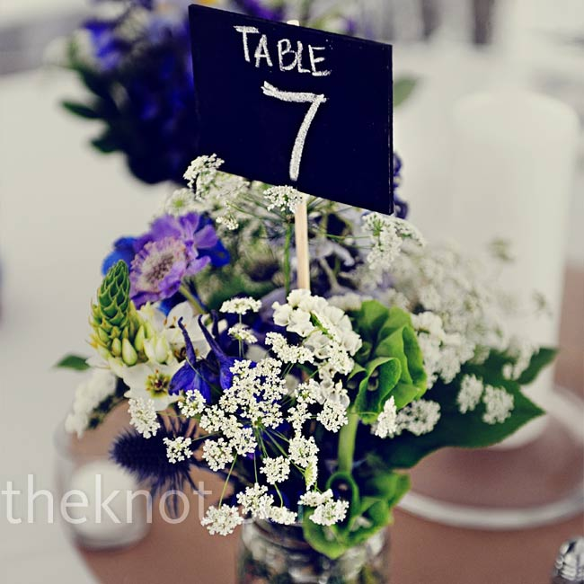 For a natural, garden feel, the centerpieces were Mason jars filled with scabiosa, viburnum, Queen Anne's lace, delphiniums, and bells of Ireland.