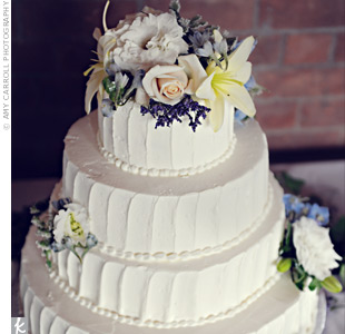 "Lisa and Greg chose a four-tiered, buttercream-frosted cake -- neither of them care for the taste of fondant. They wanted a simple design but liked the look of ""rough"" sides around the cake. Clusters of fresh roses, Queen Anne's lace, blue delphinium, lily, and lisianthus decorated the top."