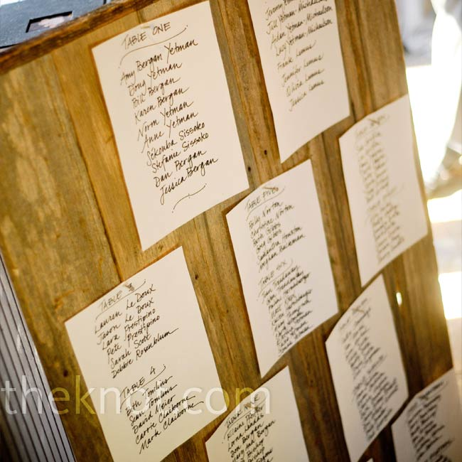 Amy and Doug didn't want to use a lot of excess paper, so to keep their reception elements rustic and green they hung the seating arrangements from an old wooden board.