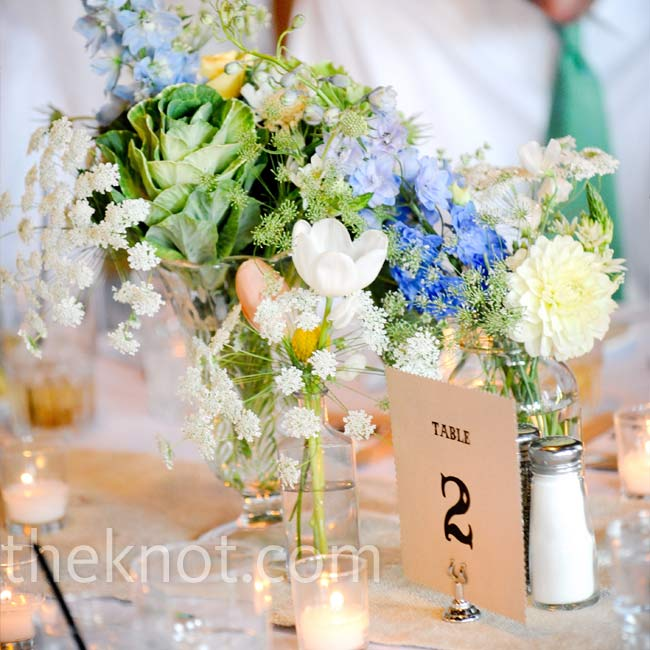 Amy used vintage vases and bottles that she had collected to complement the rustic look of the saloon. Organic-looking arrangements of succulents, hydrangeas, dahlias, delphinium, tulips, and Queen Anne's lace filled each vase.