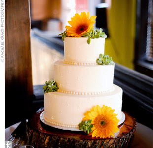 The all-white cake with buttercream beading sat atop a stump removed from the couples yard. Fresh sunflowers and Amy&#39;s favorite succulents topped the confection.