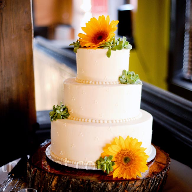 The all-white cake with buttercream beading sat atop a stump removed from the couple's yard. Fresh sunflowers and Amy's favorite succulents topped the confection.