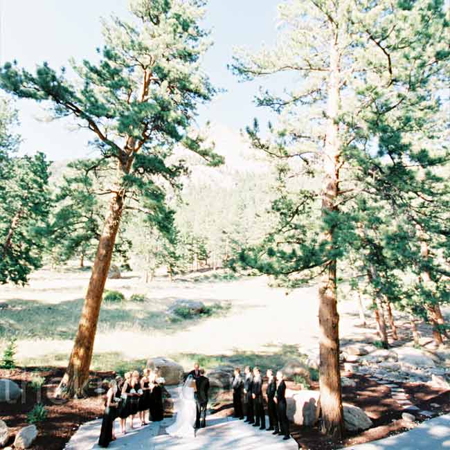 Melyssa and Adam stood on an elevated platform with Rocky Mountain National Park in the background, while their guests sat on natural stone terraces.