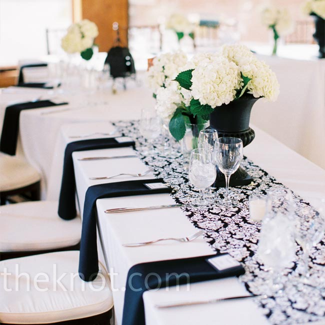Distressed black urns filled with white hydrangeas added a touch of Tuscany to the reception decor. A black-and-white runner helped the head table stand out from the rest.