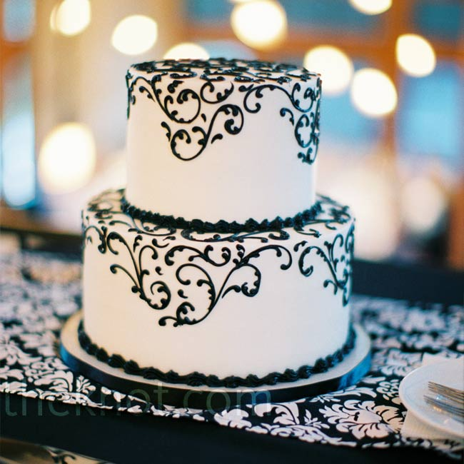 The couple cut into a small, two-tiered white buttercream cake detailed with a black swirl pattern. As an added treat, they also invited guests to a dessert bar chock-full of goodies.