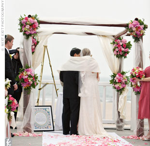 Lizzy and Howard got married beneath a huppah constructed of dark-stained bamboo wrapped with tulle. Pink rose petals added some color to the white aisle runner.