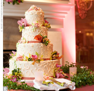 Both fresh and sugar flowers topped Lizzy and Howard's four-tiered cake, which the baker decorated with white buttercream swirls and dots.