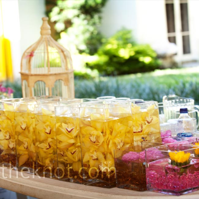 Cocktail tables were strewn with yellow tablecloths and low glass containers with fuchsia pebbles and a single floating yellow sunflower.