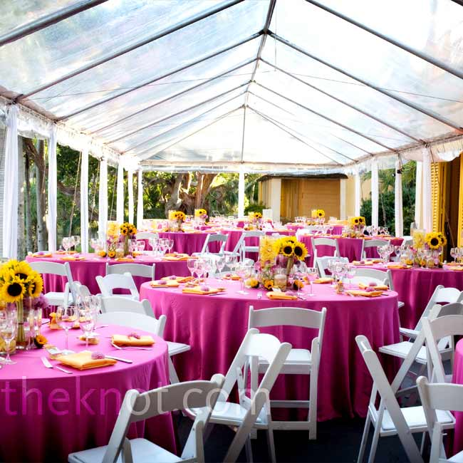 Dinner was served inside a marketplace-like tent. Tables were topped with fuchsia tablecloths and vases of varying heights filled with yellow sunflowers, fuchsia dahlias, yellow cymbidium orchids, and other bright flowers.