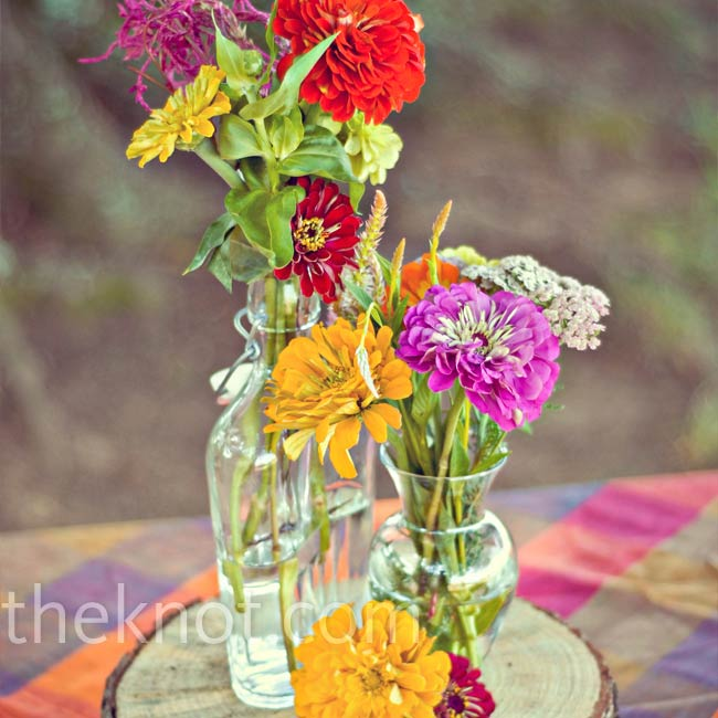 The bride shopped for a variety of antique glass vases and bottles before the wedding. They were perfect for displaying colorful wildflowers atop tree stumps on the reception tables.
