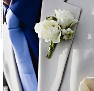 The groom wore two white roses and a cluster of white berries on his lapel.