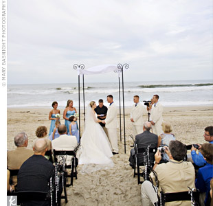 A white canopy waved in the breeze as Alicia and Scott exchanged vows. Sparkling crystals hung from black branches that were stuck in the sand along the aisle.