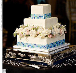 The blue mosaic pattern on the bottom tier of the cake mimicked the sequined disc detailing of the maid and matron of honor dresses and further personalized with the couples monogram. LED lights beneath the cake stand gave the crystals scattered on the table a sparkling glow.