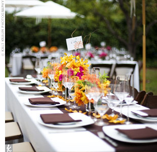 Opting for long dining tables, the couple picked low centerpieces to place along the brown table runners. The arrangements had either bright orange or bright pink dahlias wrapped in banana leaves, and stemless orange orchids were scattered down the center of the table as well.