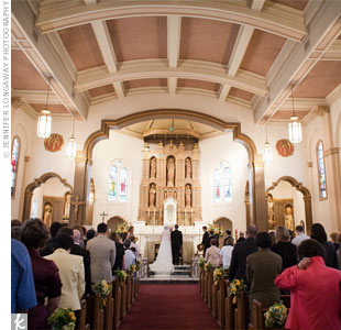 The couple opted not to decorate the church much. Two large arrangements of yellow flowers were placed on either side of the altar, and smaller arrangements marked every other pew along the aisle.