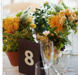 For a natural look, the florist arranged simple centerpieces of garden roses, poppies, and berries in mason jars and terra cotta pots, which guests could take home after the reception.