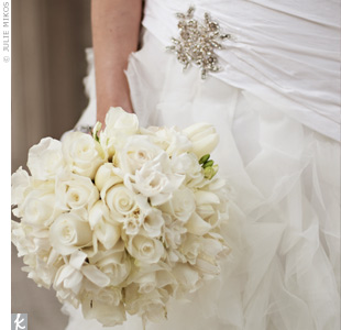 The couple decided all-white flowers would convey an elegant vibe, so Shawnti carried a full, round bouquet of white roses, freesia, French tulips, and gardenias.