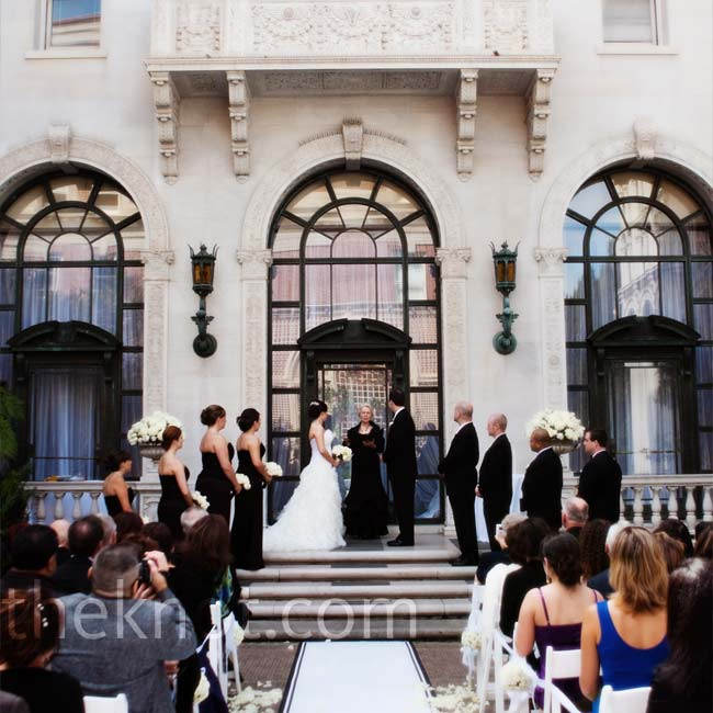 Shawnti and Andrew got married in the mansion's enclosed courtyard and stood on the steps with the building's gorgeous architecture in the background. White rose petals and a custom-made runner with their monogram marked the aisle.