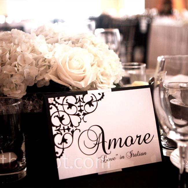 "Each table was named after the word ""love"" in a different language and marked with black and white table cards that matched the other wedding stationery. The cards were nestled next to all-white centerpieces of roses and hydrangeas."