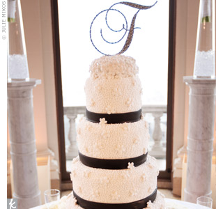 Gorgeous hand piping, handmade sugar stephanotis, and ribbons of black fondant decorated the cake's four tiers. A cluster of sugar stephanotis topped it off, along with a crystal-covered letter F for the couple's new shared initial.