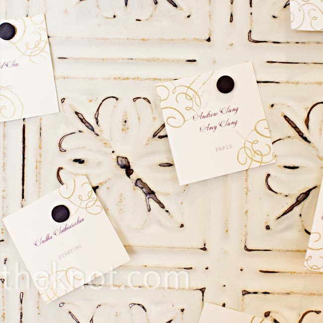 The couple's planner found antique pressed-tin ceiling panels, which made the perfect vintage background for the escort cards. Tiny magnets held the cards in place.