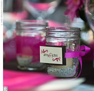 Amy and John filled mason jars with tiny rocks, put a candle inside each one, and decorated them with pink ribbon and cards with their wedding logo. They placed them on all the reception tables.