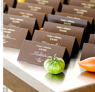 Reflection's mom harvests tomatoes in her garden, and the couple loves them, so the fruit was turned into one of the day's themes and displayed around the escort cards. Handwriting the guests' names and table numbers was a simple and pretty touch.