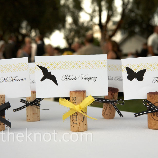 While dating, Sabena and Kevin began saving corks from the wines they drank together. They finally found a good use for them -- a simple slit on the top made the perfect opening for the escort cards. Ribbon tied around the corks finished off the look.