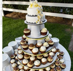 Sabena and Kevin served cupcakes for a lighter, more fun feel than a tiered wedding cake. For tradition's sake, they cut into a small cake with a black scalloped edge and yellow sugar flowers cascading down the side.
