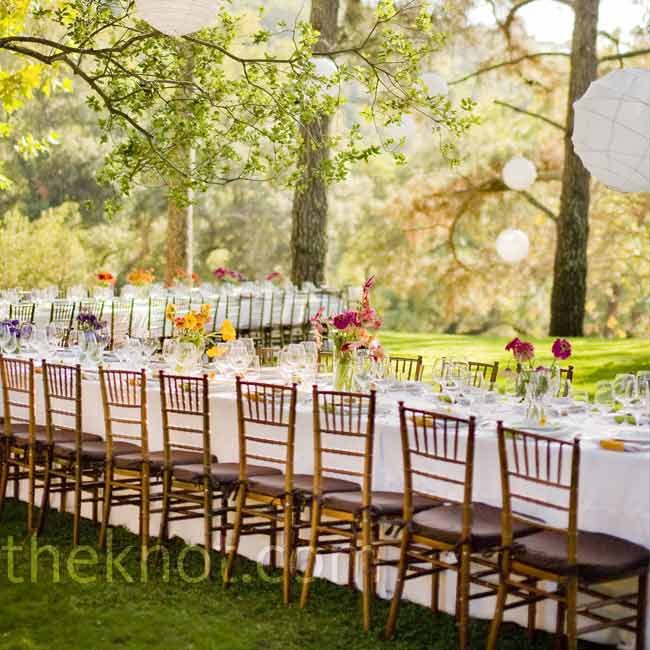 Sarah and Jason wanted their wedding to feel like a big dinner party for their 51 guests. They set up two long dining tables on the grass and chose white linens to play up the colorful centerpieces.