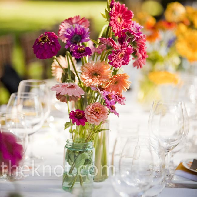 Light arrangements of red, pink and coral daisies were set in blue and clear mason jars for a fun, pretty look that worked well with the polka dot plates.
